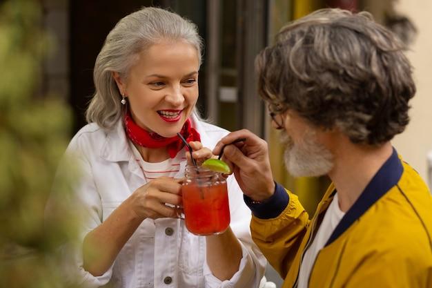 In gezelschap van een geliefde. gelukkig getrouwd stel brengt hun tijd door in het café en drinkt een smoothie.
