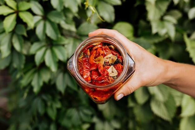 In haar hand heeft ze een open pot met zongedroogde tomaten met olijfolie.