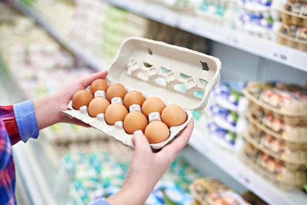 In handen van vrouwen verpakkende eieren in supermarkt