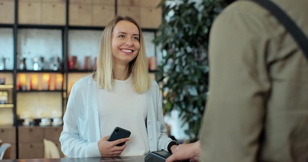In het café maakt de barista-man afhaalkoffie voor een vrouwelijke klant die met een contactloze mobiele telefoon aan het creditcardsysteem betaalt.