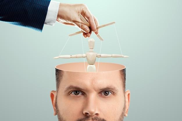 In het hoofd van de man is een pop een pop in plaats van een brein. het concept van verslaving, slaaf, gecontroleerde persoon, vervelende werknemer, klerk, kantoorplankton.