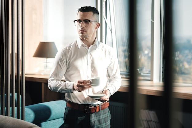 In het kantoor. jonge welvarende knappe man die in zijn kantoor bij het raam met de kop koffie