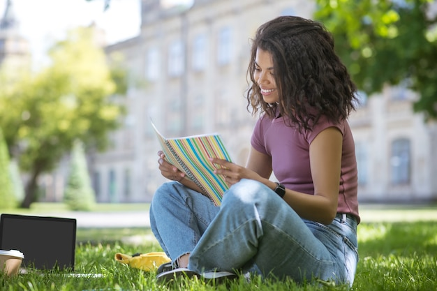 In het park. een mooi meisje in een roze t-shirt zittend op het gras in het park en studeren