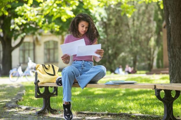 In het park. een schattig meisje in spijkerbroek wandelen in het park
