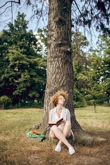 In het park. jonge vrouw zittend onder de boom in het park