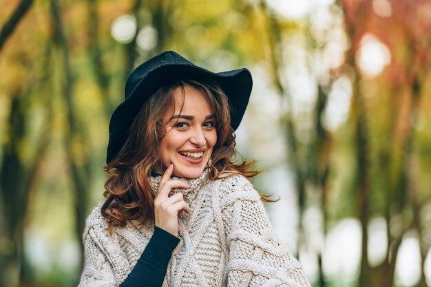 In het park staat een meisje met een zwarte hoed met een charmante glimlach