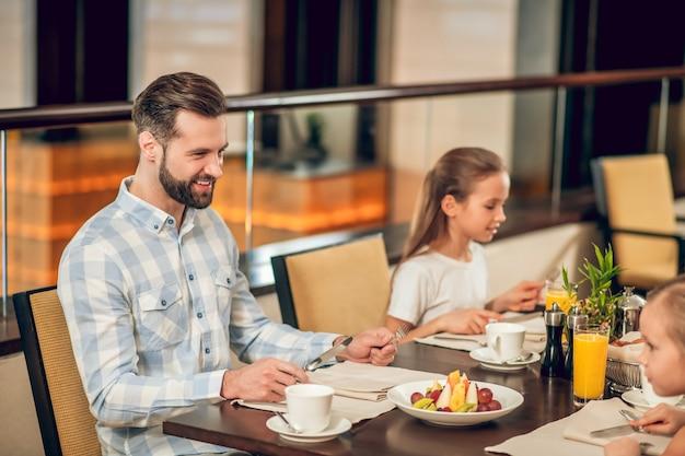 In het restaurant. zittend aan de tafel in het restaurant en gelukkige familie