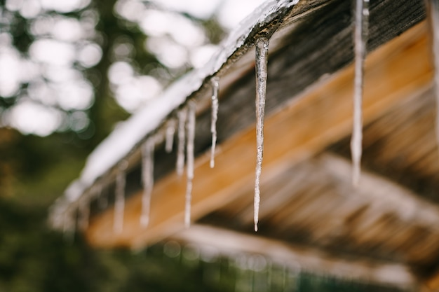 In het voorjaar hangen ijspegels aan een houten dak