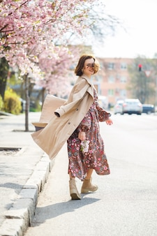 In het voorjaar loopt een vrouw langs een bloeiende straat met sakurabomen. een meisje in een lange, elegante vintage jurk van zijde loopt tussen de bloeiende bomen