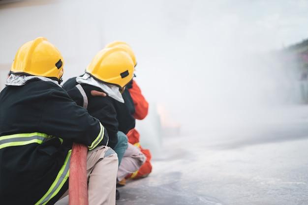 In het vuur, dappere brandweerman met behulp van brandblusser en water uit de slang voor brandbestrijding