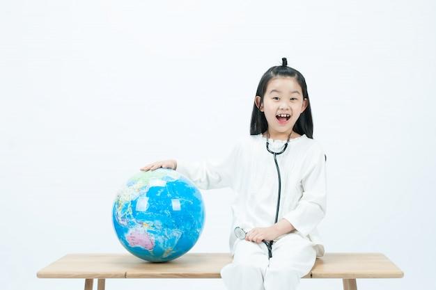 In het wit lacht een kind op een houten stoel fel met een stethoscoop op de wereldbol.