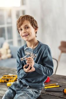 In hogere sferen. mooie vrolijke blonde jongen die lacht en een vergrootglas vasthoudt terwijl hij op de tafel zit