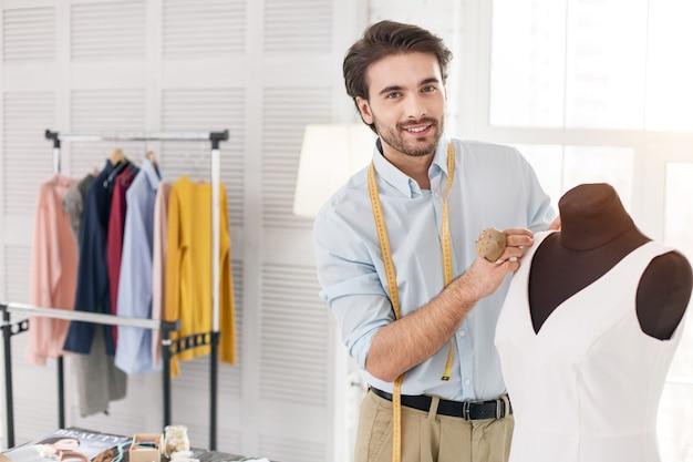 In hogere sferen. opgetogen donkerharige kleermaker die in zijn kantoor werkt en een nieuwe jurk maakt