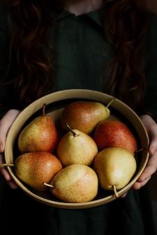 In je handen ligt een bord met een verse perenoogst.
