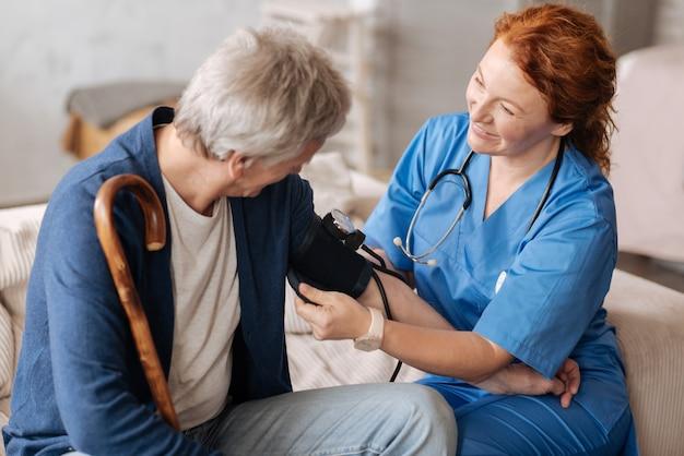 In je mouw. charmante, nette, zorgvuldige dame met behulp van een speciaal apparaat voor het controleren van de bloeddruk van patiënten tijdens het uitvoeren van een algemeen onderzoek