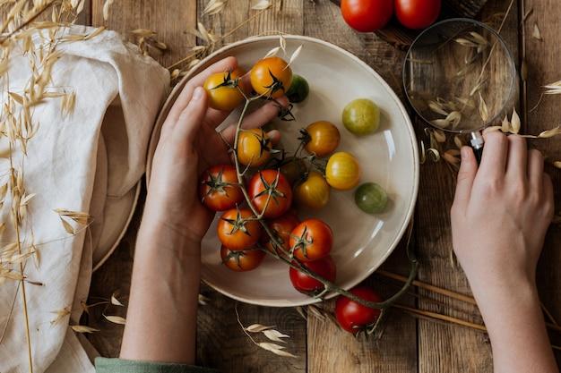 In kinderhanden een bord met kleine tomaten op een tak.