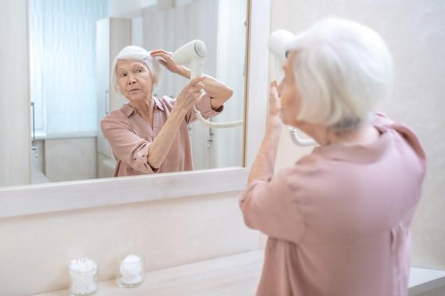 In kuuroord. grijsharige rijpe vrouw haar haren drogen in een kleedkamer in het kuuroord