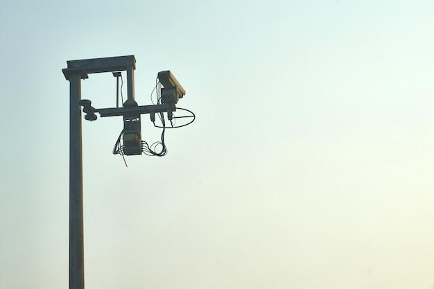In openlucht kringscamera bij weg of tolmanier door ambtenaar of politie voor veiligheid op blauwe hemelachtergrond