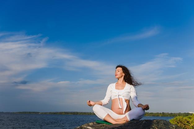 In openlucht mediterende zwangere vrouw.