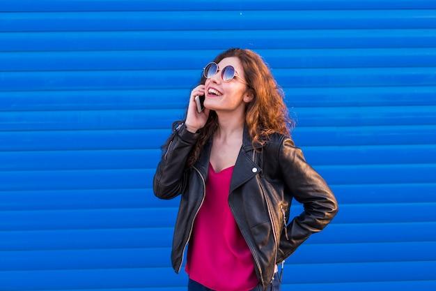 In openlucht portret van een mooie jonge vrouw die op haar slimme telefoon over blauw spreekt
