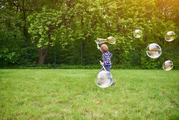 In openlucht portret van leuke peuterjongen blazende zeepbels op een groen gazon bij de speelplaats