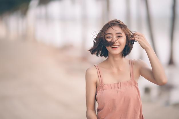 In openlucht portret van mooi jong meisje dat op strand lacht. het aziatische vrouw geschotene haar glimlachen en bekijkt camera; vrij van kopie ruimte.