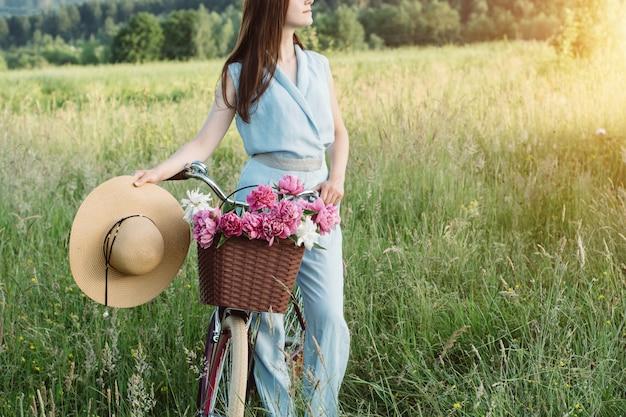 In openlucht portret van mooie vrouw die een fiets houdt