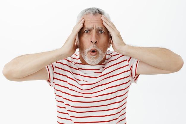 In paniek geschokt, bebaarde senior man die in paniek raakte en gealarmeerd keek