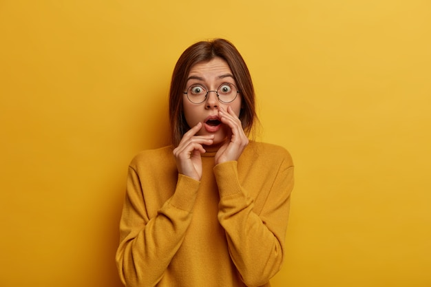 In paniek geschokte europese vrouw voelt zich teleurgesteld en onder de indruk, hoort iets ongelooflijks, draagt een ronde bril en een losse trui, geïsoleerd over een gele muur, staat sprakeloos.