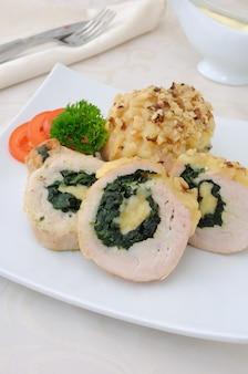 In plakjes gesneden kiprollade gevuld met spinazie en mozzarella en kaas met walnoot