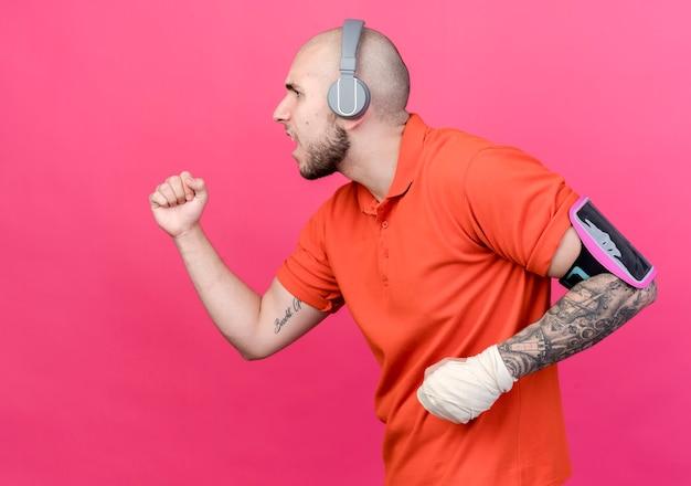In profiel bekijken sportieve jongeman met pols verband hoofdtelefoon dragen met telefoon armband doen alsof rennen geïsoleerd op roze achtergrond