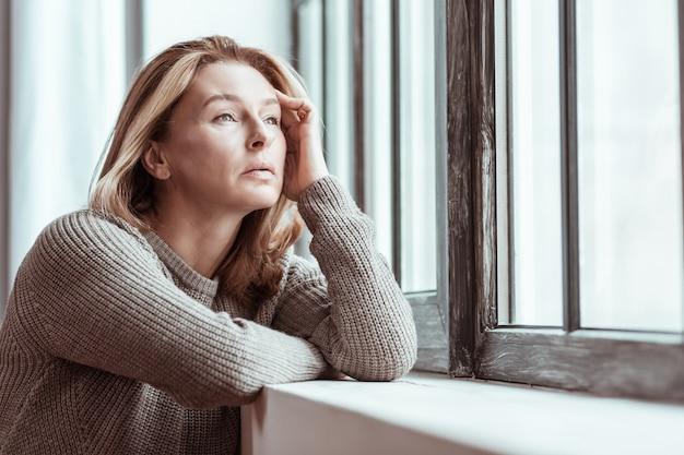 In raam kijken. mooie rijpe vrouw die zich gestrest voelt terwijl ze naar het raam kijkt terwijl ze thuis blijft