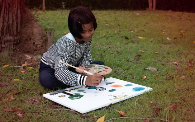 In selectieve aandacht van klein meisje hand met behulp van penseelverf kleur op canvas, wazig licht rond