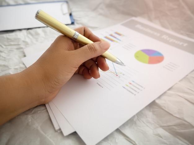 In selectieve focus van menselijke hand met pen en schrijven op wazig zakelijke papieren grafiek