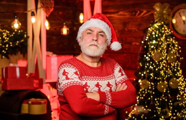 In slechte stemming. bebaarde man kerstmuts. vrolijk kerstfeest. vrolijke kerstman rode trui. gelukkig nieuw 2020 jaar. warme kleding in het koude seizoen. kerstcadeaus en cadeautjes. winter vakantie. tijd voor een feestje.
