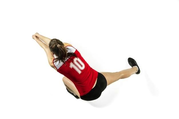 In sprong en vlucht. jonge vrouwelijke volleyballer die op witte studioachtergrond wordt geïsoleerd. vrouw in sportkleding en sneakers trainen, spelen. concept van sport, gezonde levensstijl, beweging en beweging.