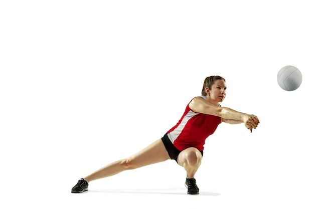 In sprong en vlucht. jonge vrouwelijke volleyballspeler die op witte studioachtergrond wordt geïsoleerd. vrouw in sportkleding en sneakers trainen, spelen. concept van sport, gezonde levensstijl, beweging en beweging.