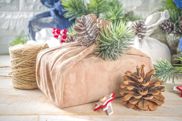 In stof verpakte kerstcadeaus. herbruikbaar duurzaam en zero waste concept, geschenkverpakking van gerecycled textiel. milieuvriendelijke kersttradities en decoraties. kerstcadeaus in japanse furoshiki-stijl