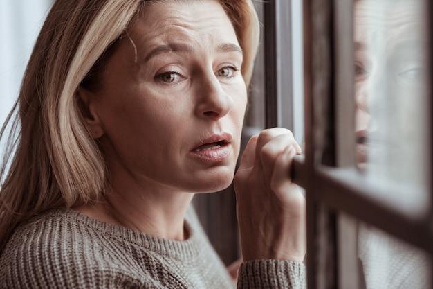 In tranen uitbarsten. blondharige depressieve volwassen vrouw die zich gestrest voelt en in tranen uitbarst