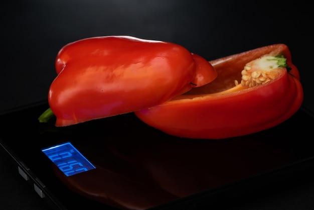 In tweeën gesneden rode peper is op een elektronisch gewicht op een zwarte achtergrond.
