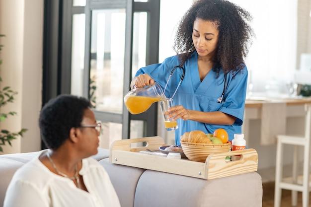 In verpleeghuis. verpleegster die wat sinaasappelsap schenkt en ontbijt brengt voor dame die in verpleeghuis woont
