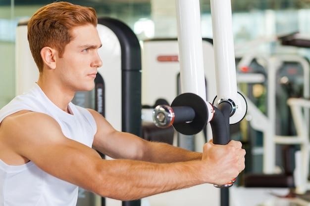 In vorm blijven is erg belangrijk. geconcentreerde jonge en sportieve man aan het trainen in de sportschool