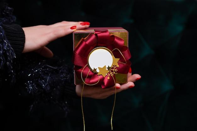 In vrouw hand aanwezig is, met mooie rode geschenkdoos met kopie ruimte, close-up foto op donkere achtergrond. kerstmis.
