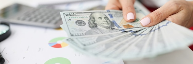 In vrouwelijke handen zijn honderd-dollarbiljetten op tafel commerciële en financiële cijfers in grafieken