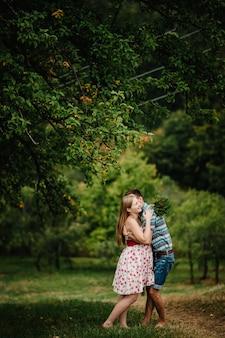 In wachtende baby. gelukkig gezin. zwangere vrouw met geliefde echtgenoot omhelzing, blootsvoets op het gras. ronde buik. het oprechte tedere moment. achtergrond, natuur, park, boom, bos, negen maanden. blijheid