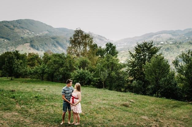 In wachtende baby. gelukkig gezin. zwangere vrouw met geliefde echtgenoot staat, houdt hand rond buik op blote voeten op het gras. de oprechte tedere momenten. achtergrond, bergen, bossen, natuur, negen maanden
