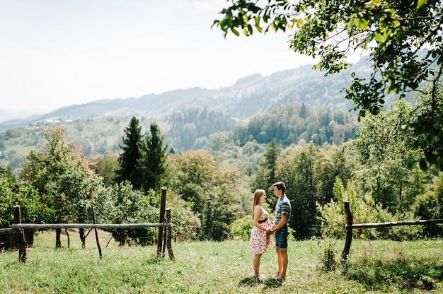 In wachtende baby. gelukkig gezin. zwangere vrouw met geliefde man staan hand in hand op het gras. ronde buik. ouderschap. de oprechte tedere momenten. achtergrond, bergen, bossen, natuur