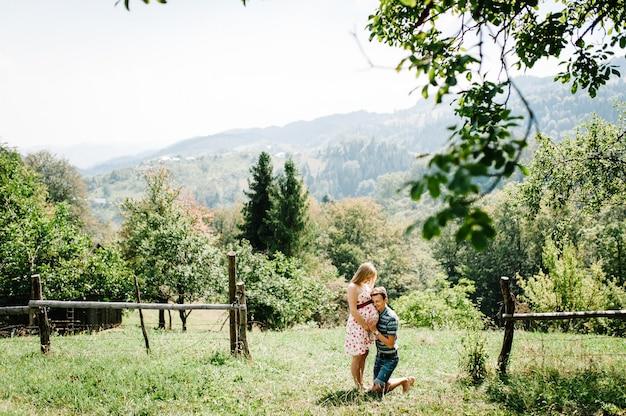 In wachtende baby. zwangere vrouw met geliefde man staan op het gras. ronde buik. man geknield omhelst vrouw een ronde buik. ouderschap. de oprechte tedere momenten. bergen, bossen, natuur