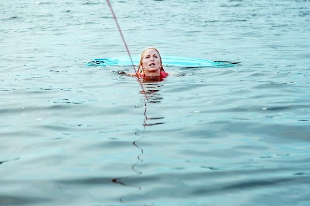 In water. mooie blonde blanke vrouw in een roze reddingsvest drijvend in de rivier terwijl ze een sleeptouw vasthoudt