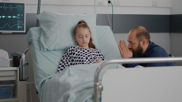 In ziekenhuisafdeling slaapt kleine kindpatiënt terwijl bezorgde vader bidt voor herstel van de ziekte